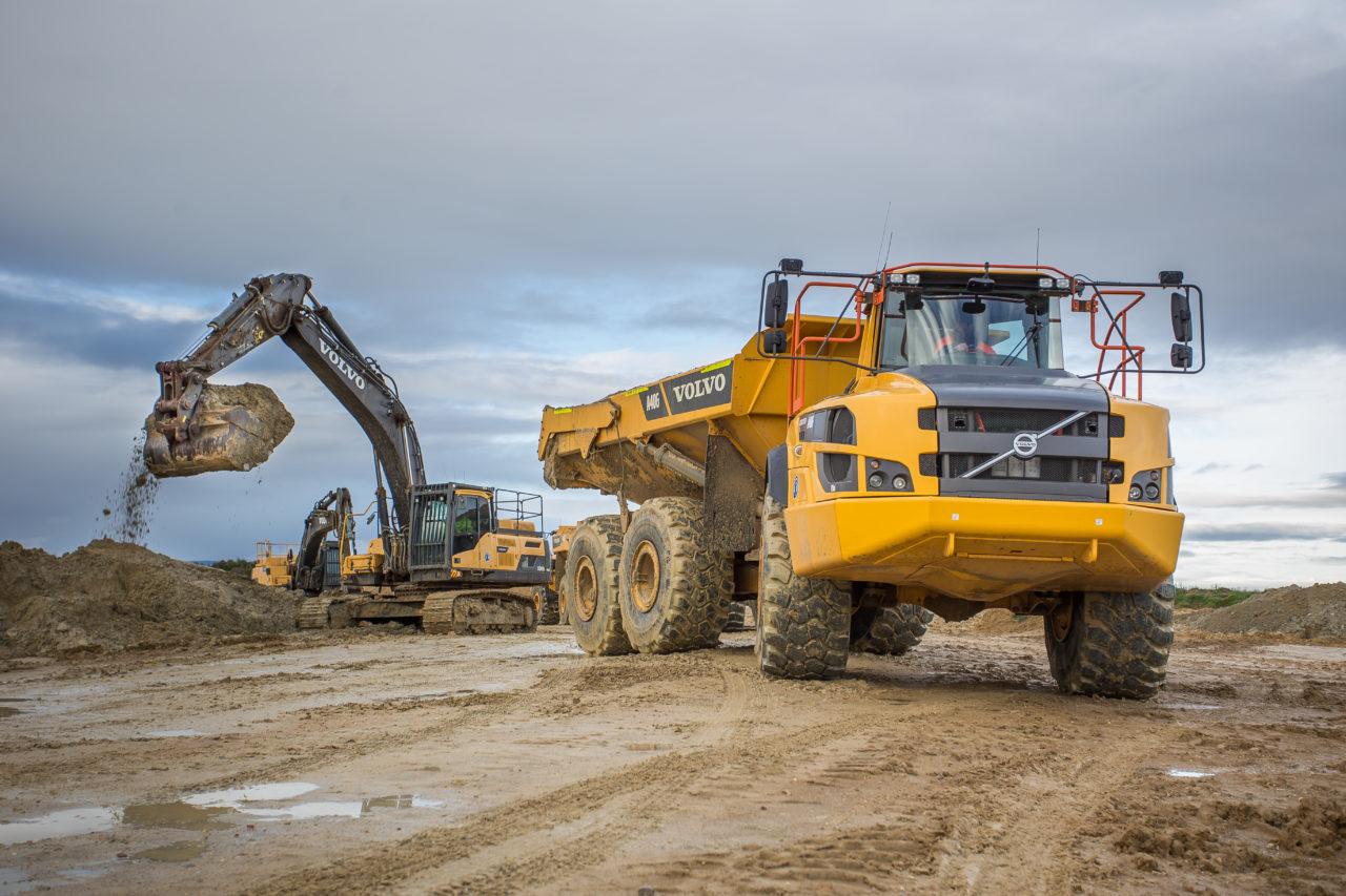 two volvo trucks at a worksite