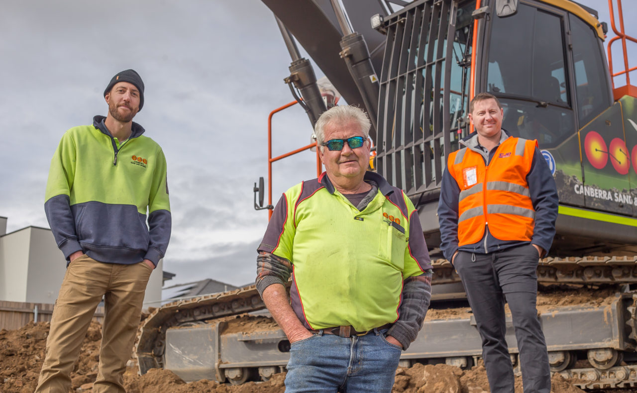 three men standing next to a piece of heavy machinery